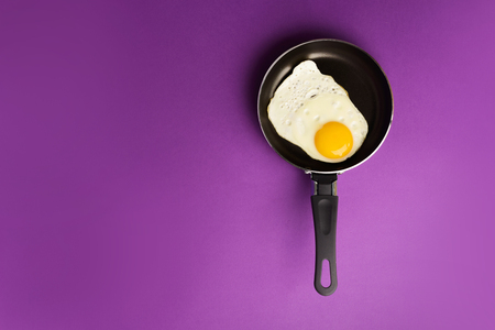 Creative food concept with fried egg on pan over blue background. Top view. Creative pattern in minimal style. Flat lay. Reklamní fotografie - 122063338