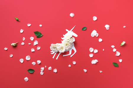 Creative layout. White unicorn with flowers over coral paper