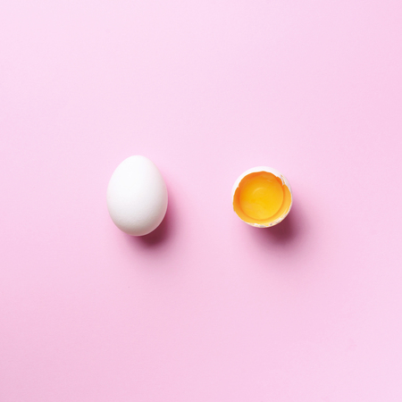Food concept with broken egg and whole one on pink background. Top view. Creative pattern in minimal style. Flat lay. Square crop.