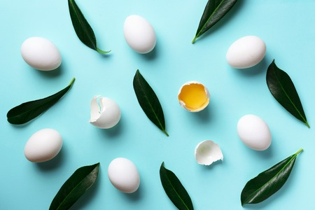 Food concept with white eggs, green leaves on blue color. Top view. Creative pattern in minimal style. Flat lay Zdjęcie Seryjne