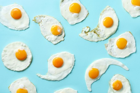 Fried eggs or scrambled eggs pattern on blue background. Creative food concept. Top view.