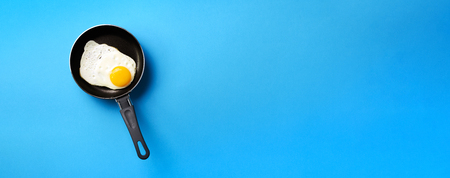 Creative food concept with fried egg on pan over blue background. Top view. Creative pattern in minimal style. Flat lay. Banner.