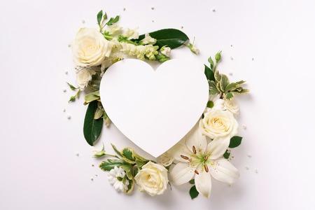 Marco de flores blancas, corazón de papel sobre fondo claro. Día de San Valentín, concepto de día de la mujer. Banner de primavera o verano con espacio de copia. Foto de archivo