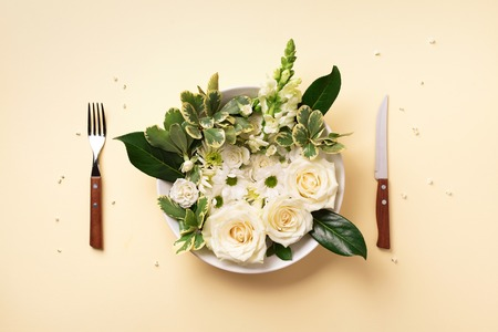 White flowers on plate, fork, knife over pastel yellow background. Healthy eating, vegan diet concept. Creative layout. Top view, flat lay. Banco de Imagens