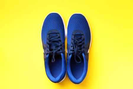 Pair of blue sport shoes on yellow background. Top view, copy space. Fitness, running and sport concept. Healthy lifestyle. 版權商用圖片