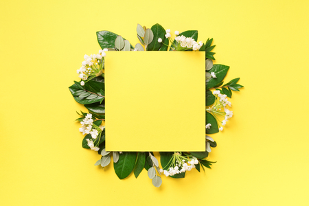 Summer and spring concept. Tropical nature background with green leaves, white flowers and white empty square frame for copy space on yellow paper. Top view. Flat lay. Creative advertising.