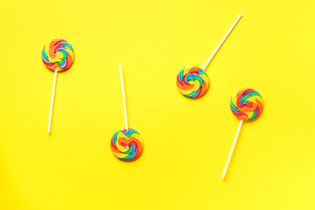 Round colorful lollipops on yellow background. Top view. Confetti for holidays, birthday party concept.