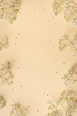 Small white gypsophila flowers on pastel yellow background. Womens Day, Mothers Day, Valentines Day, Wedding concept. Flat lay. Top view. Copy space.
