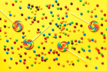 Multicolored lollipop, rainbow colorful candies on yellow background. Coated chocolate sweet pieces texture. Top view. Flat lay. Confetti for holidays, birthday party concept. Stok Fotoğraf