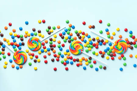 Multicolored lollipop, rainbow colorful candies on blue background. Coated chocolate sweet pieces texture. Top view. Flat lay. Confetti for holidays, birthday party concept.