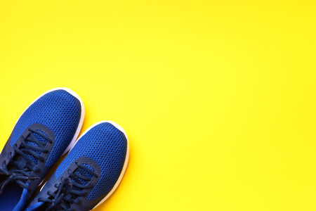 Pair of blue sport shoes on yellow background. Top view, copy space. Fitness, running and sport concept. Healthy lifestyle. Stok Fotoğraf