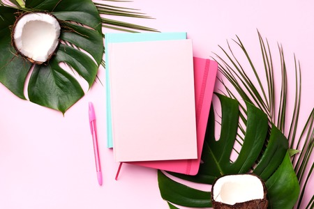 Green monstera, palm leaves, coconut, notebooks over pink background. Female blog writer workspace concept. Flat lay. Top view