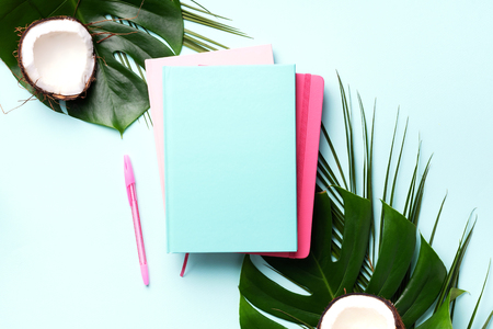 Female blog writer workspace concept. Green monstera palm leaves, coconut on pink background with copy space. Banner. Flat lay, top view