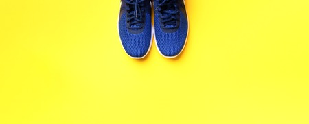 Pair of blue sport shoes on yellow background. Top view, copy space. Fitness, running and sport concept. Healthy lifestyle. Banner.