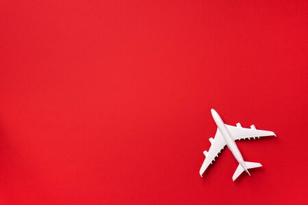 White plane, airplane on red color background with copy space. Top view, flat lay. Minimal style design. Travel, vacation concept.