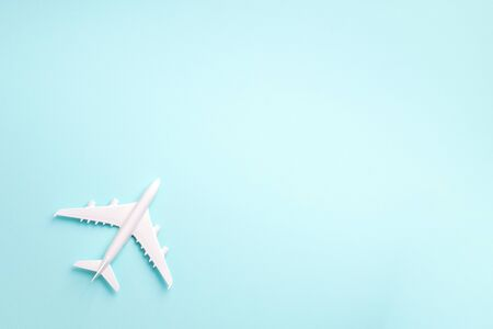 White plane, airplane on blue pastel color background with copy space. Top view, flat lay. Minimal style design. Travel, vacation concept.