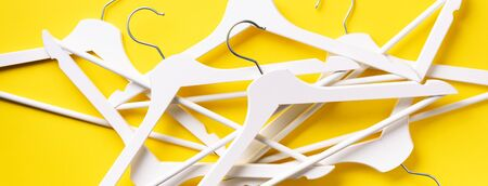Top view of white clothes hangers on yellow background with copy space. Flat lay. Minimalism style. Creative layout. Fashion, store sale, shopping concept. Banner for feminine blog.