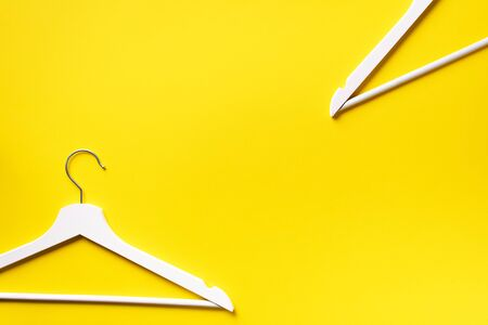 White clothes hangers on yellow background with copy space. Flat lay. Top view. Minimalism style. Creative layout. Fashion, store sale, shopping concept. Banner for feminine blog.