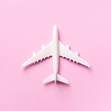 Travel, vacation concept. White model airplane on pastel pink color background with copy space. Top view. Flat lay. Minimal style design. Square crop. Stok Fotoğraf