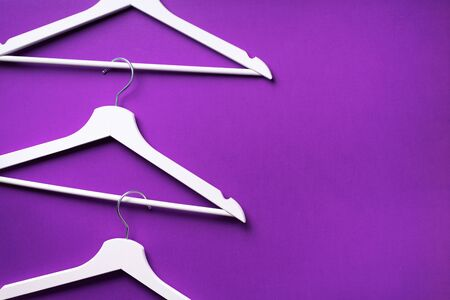 White clothes hangers on violet background with copy space. Flat lay. Top view. Minimalism style. Creative layout. Fashion, store sale, shopping concept. Banner for feminine blog. Stok Fotoğraf