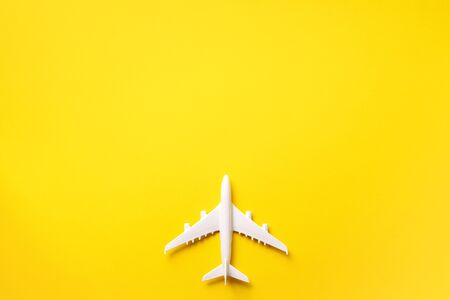 Travel, vacation concept. White model airplane on yellow color background with copy space. Top view. Flat lay. Minimal style design
