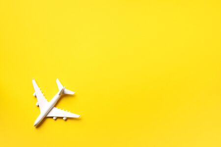 Creative layout. Top view of white model plane, airplane toy on yellow background. Flat lay with copy space. Summer trip or travel concept.