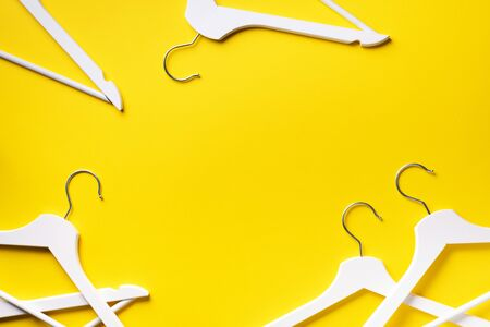 Top view of white clothes hangers on yellow background with copy space. Flat lay. Minimalism style.