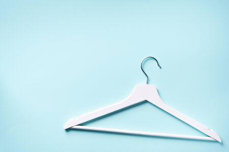 Vista superior de la percha de ropa blanca sobre fondo azul con espacio de copia. Endecha plana.