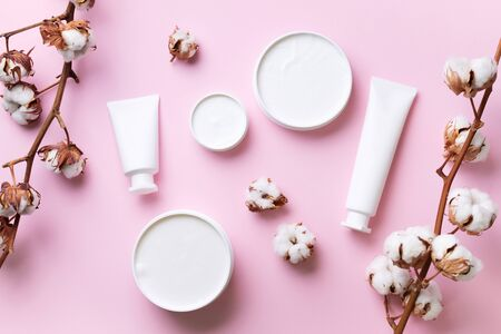 Fluffy cotton flowers, face cream, body butter on pink background with copy space. Cosmetics, beauty, spa concept. Top view. Flat lay. Stock fotó