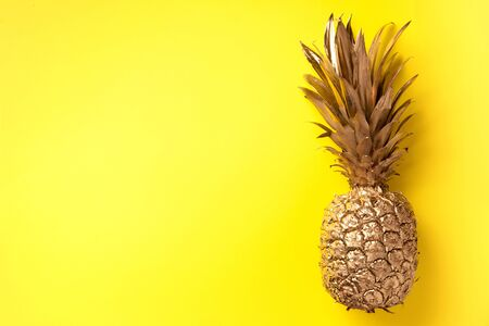 Creative layout. Gold pineapple on yellow background with copy space. Top view. Tropical flat lay. Exotic food concept, crazy trend. Banner.