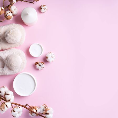 Bathroom accessories, nude fluffy home slippers, cotton flowers, candle, skin care products on pink background with copy space. Top view. Copy space. Spa and body treatment concept