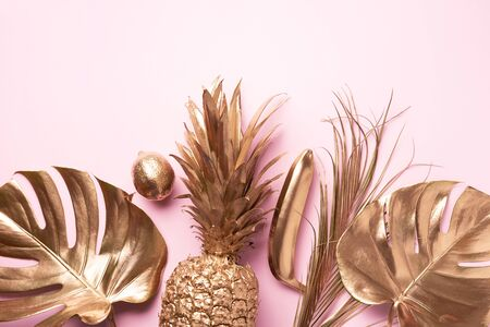 Golden exotic fruits, tropical palm, monstera leaves on pink background. Top view. Flat lay. Food concept. Creative layout of gold pineapple, banana, lemon with copy space