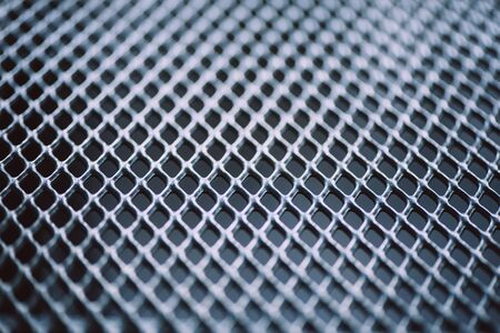 Surface of latticed metal fence. Stainless steel and aluminum light blur background. Macro texture. Imagens