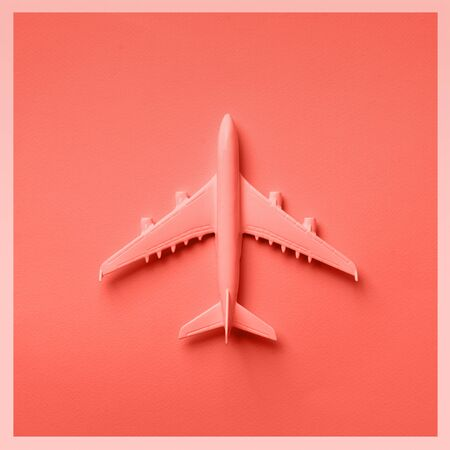 Creative layout. Top view of white model plane, airplane toy on pink pastel background. Flat lay with copy space. Trip or travel banner in trendy coral color.