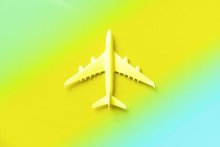 White plane, airplane in trendy neon colors. Rainbow gradient background with copy space. Top view, flat lay. Minimal style design. Travel, vacation concept. Banner Stockfoto