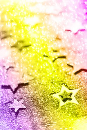Christmas celebration. Abstract background for new year party. Patter of gold stars with lights, bokeh over neon color background. Golden glitter stars in trendy violet, purple and yellow colors.