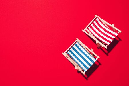 Flat lay of beach deck chairs on red background with copy space. Summer and travel concept. Creative banner. Reklamní fotografie