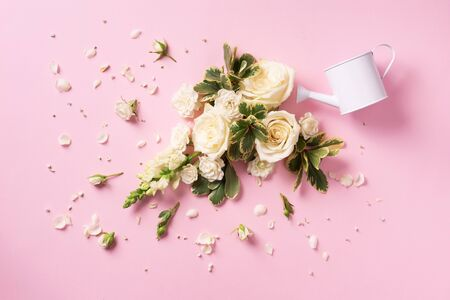 Watering can and white rose flowers, petals over pink background. Ideas for creative business. Summer, spring or gardening concept
