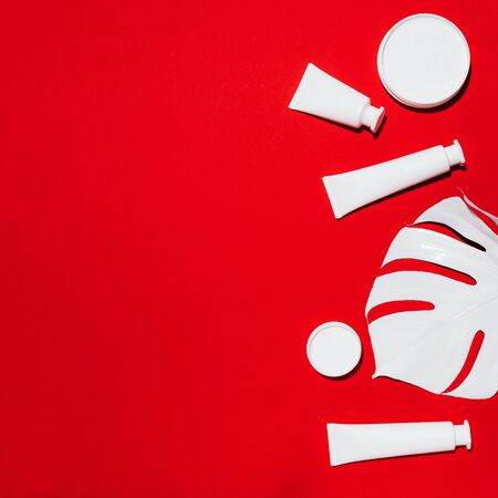 White bottles of skin care creams, monstera leaf over red background with copy space. Top view. Flat lay. Cosmetics, beauty, body treatment concept.