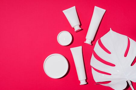 Cosmetic set of white bottles, monstera leaf over pink background. Natural beauty product concept
