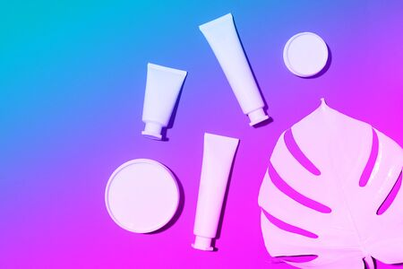 Cosmetics, skin care, beauty, body treatment concept. White cosmetic jar, tube, bottle and tropical monstera leaf over neon background. Top view. Flat lay. Mock-up