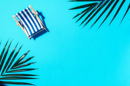 Deck chair with hard shadow, palm leaves on blue paper background. Flat lay and copy space. Summer travel vacation concept. Minimal composition 스톡 콘텐츠