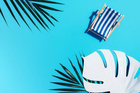 Deck chair with hard shadow, monstera and palm leaves on blue paper background. Flat lay and copy space. Summer travel vacation concept. Minimal composition