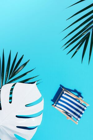 Flat lay of beach deck chair, monstera and palm leaves on blue background with copy space. Summer and travel concept. Creative banner 스톡 콘텐츠