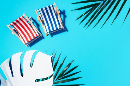 Two deck chairs with hard shadow, monstera and palm leaves on blue paper background. Flat lay and copy space. Summer travel vacation concept. Minimal composition