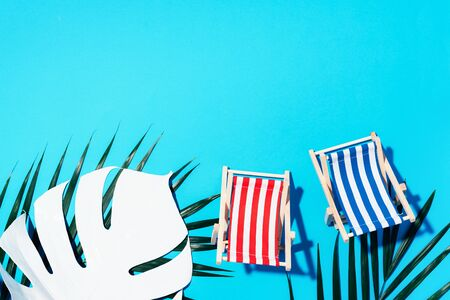Flat lay of beach deck chairs, monstera and palm leaves on blue background with copy space. Summer and travel concept. Creative banner