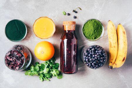 Blueberries, bilberry, barley grass, spirulina, orange juice, dulse, cilantro on marble background. Top view. Healthy eating, alkaline diet, vegan concept. Ingredients of heavy metals detox smoothie