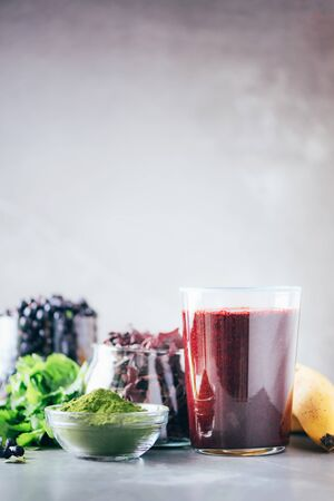 Heavy metals detox smoothie. Blueberries, bilberry, barley grass juice extract, spirulina powder, orange juice, dulse and cilantro on gray background. Healthy eating, alkaline diet, vegan concept