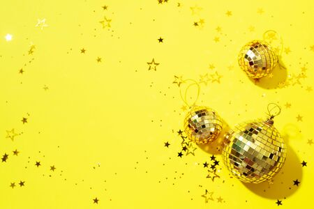 Creative Christmas concept. Shiny gold disco balls over yellow background. Flat lay, top view. New year baubles, star sparkles. Party time. Greeting card. Stock Photo