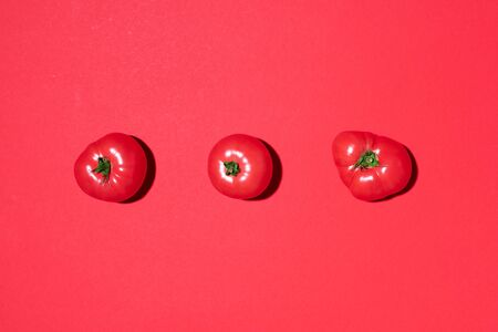 Red tomatoes pattern on red background. Flat lay, top view. Summer minimal concept. Vegan and vegetarian diet.